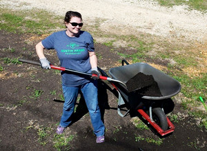 member adding compost to plot